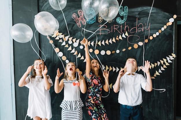 Aufgeregte kinder, die ballone auf party freigeben Kostenlose Fotos