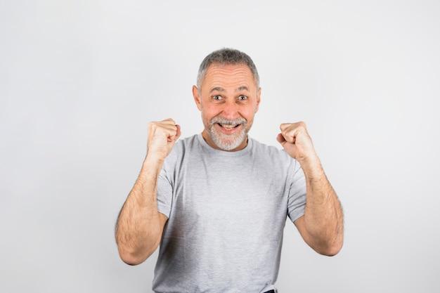 Aufgeregter älterer mann, der oben aufmuntert Kostenlose Fotos