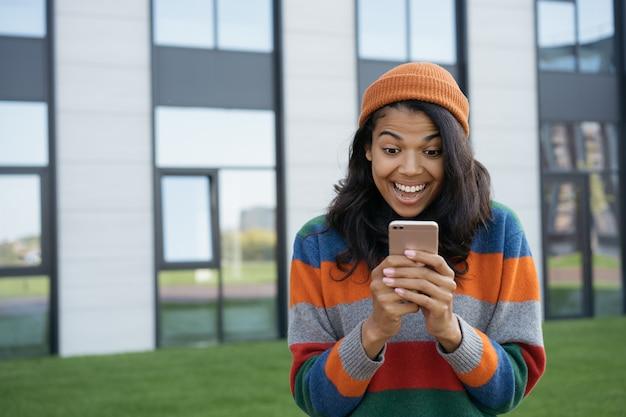 Aufgeregter afroamerikaner, der handy benutzt Premium Fotos