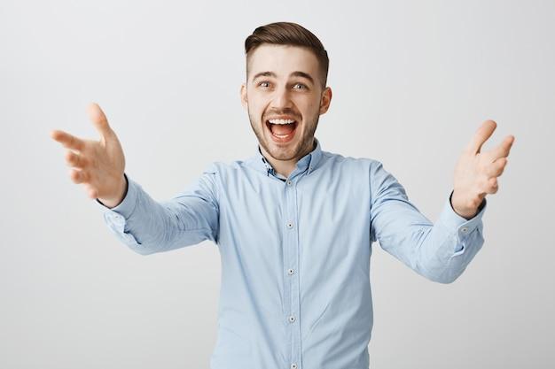 Aufgeregter glücklicher geschäftsmann, der hände greift, um jemanden zu begrüßen, preis zu nehmen, produkt zu halten Kostenlose Fotos