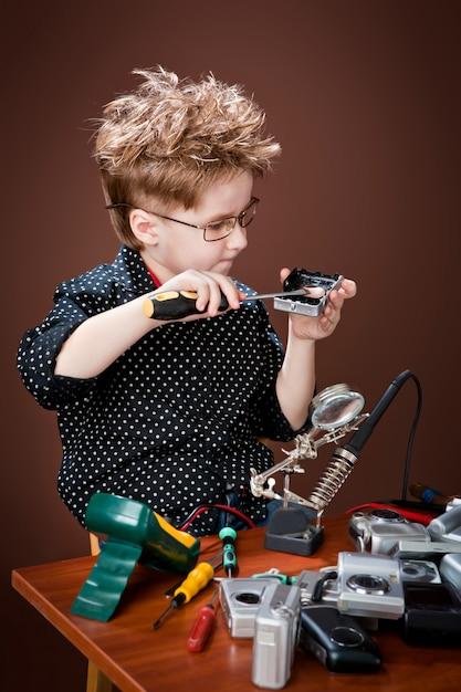 Aufgeregter junge lächelt und repariert kameras. Premium Fotos