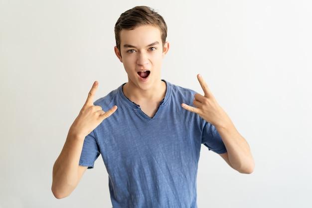 Aufgeregter junger mann, der hornzeichen zeigt und an der kamera schreit Kostenlose Fotos