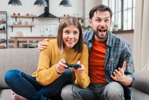 Aufgeregter junger mann, der mit ihrer frau spielt das videospiel sitzt Kostenlose Fotos