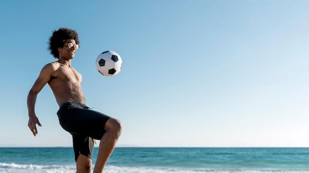 Aufgeregter junger schwarzer mann, der ball auf küste schlägt Kostenlose Fotos