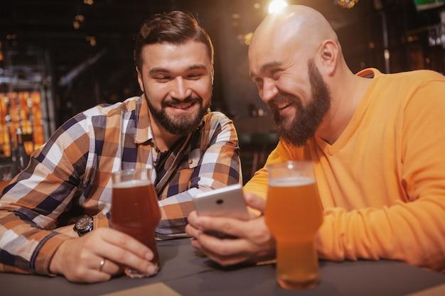 Aufgeregter mann, der seinem freund etwas online zeigt, während er zusammen trinkt Premium Fotos