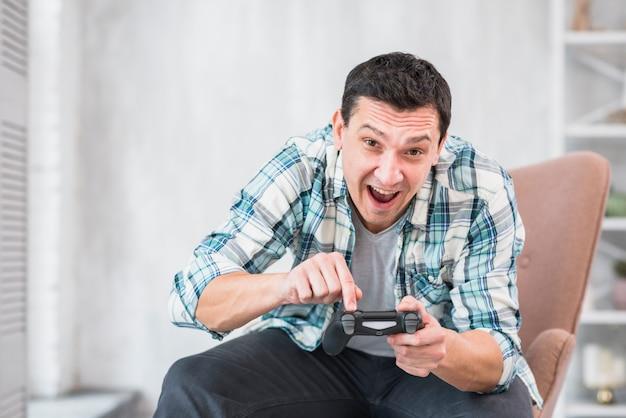Aufgeregter mann, der zu hause mit gamepad spielt Kostenlose Fotos