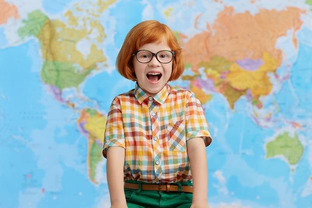 Aufgeregter rothaariger kleiner junge in großen gläsern und kariertem hemd, der vor freude den mund öffnet, während er im klassenzimmer steht, sich freut, seine eltern zu sehen und nach hause zurückzukehren. kluges kleines kind Kostenlose Fotos