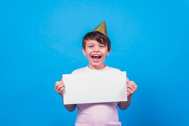 Aufgeregter tragender partyhut des kleinen jungen, der in der hand leere karte auf blauer oberfläche hält Kostenlose Fotos
