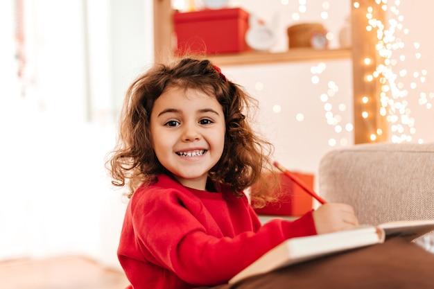 Aufgeregtes kind, das mit lächeln zeichnet. innenaufnahme des brünetten kindes mit stift und notizbuch. Kostenlose Fotos