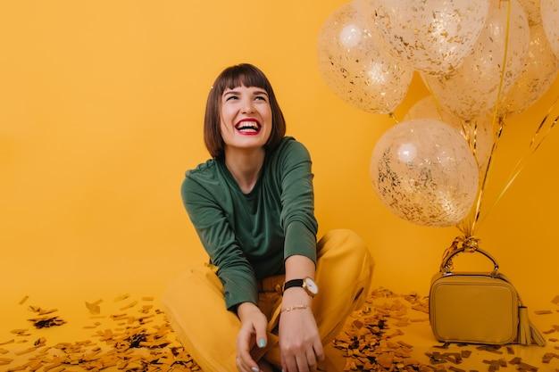 Aufgeregtes mädchen im grünen pullover, das glücklich mit partyballons lacht. innenaufnahme der raffinierten kaukasischen frau, die wahre positive gefühle ausdrückt. Kostenlose Fotos