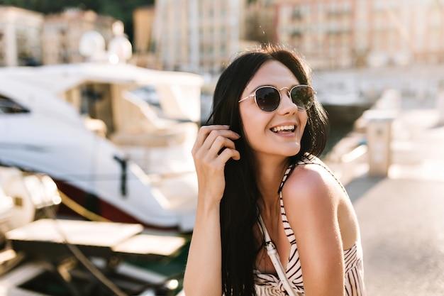 Aufgeregtes mädchen mit langen schwarzen haaren, die glücklich lachen, während sie draußen mit booten sitzen Kostenlose Fotos