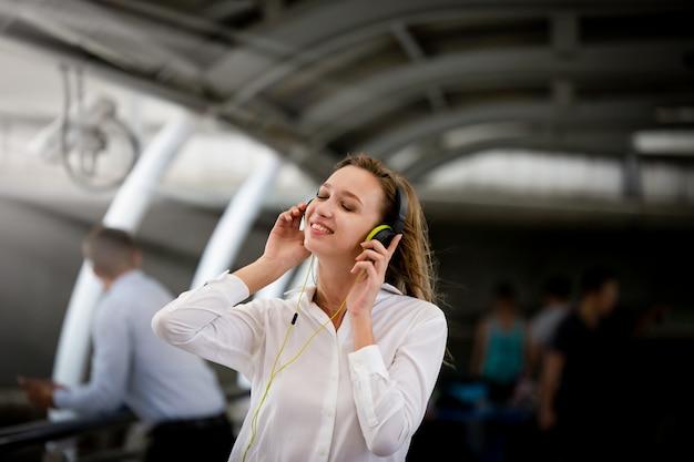 Aufgeregtes mädchentanzen und hörende musik mit kopfhörern in der straße mit glück Premium Fotos