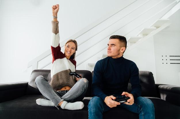 Aufgeregtes nettes mädchen feiern das gewinnen, hoben ihre faust oben an, nachdem sie computerspiele gespielt haben Kostenlose Fotos