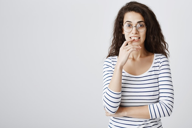 Aufgeregtes neugieriges mädchen in der brille, das finger beißt und interessiert schaut Kostenlose Fotos