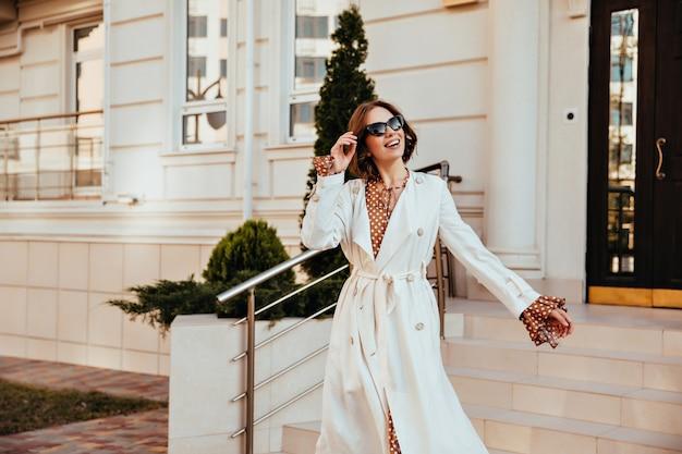 Aufgeregtes weibliches modell im langen weißen kittel, das guten tag genießt. außenaufnahme der aktiven jungen frau im herbstoutfit. Kostenlose Fotos