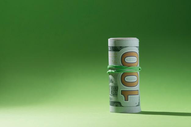 Aufgerollte banknoten auf grüner oberfläche Kostenlose Fotos