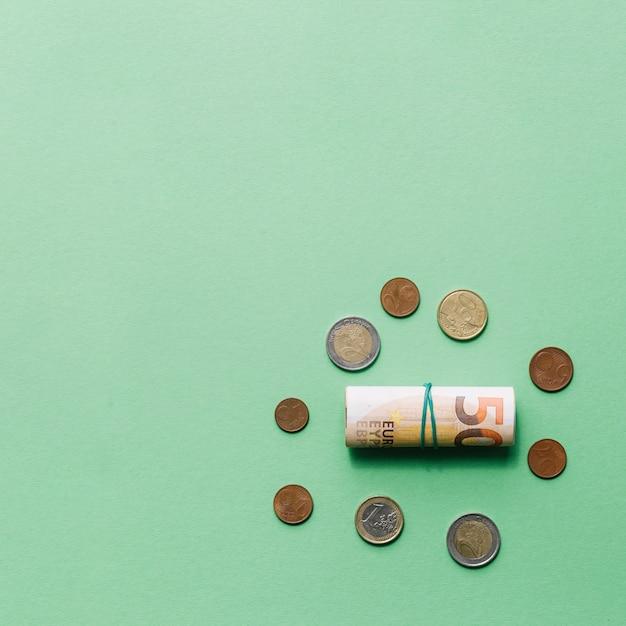 Aufgerollte euro-banknote mit münzen auf grünem hintergrund Kostenlose Fotos