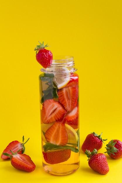 Aufgossenes wasser mit erdbeere und zitrone in der flasche Premium Fotos