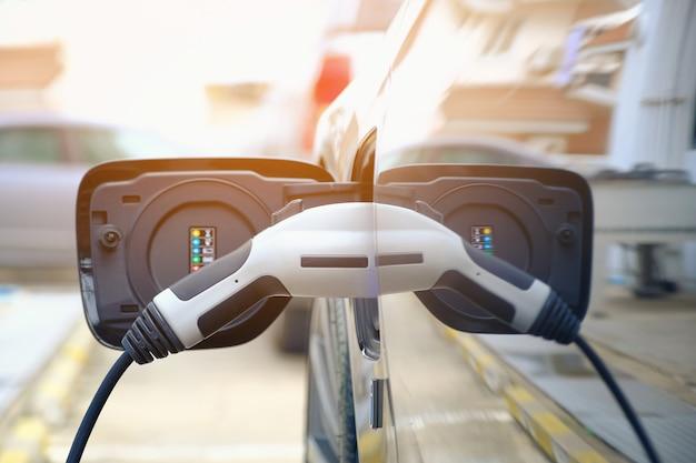 Aufladen der modernen elektroautobatterie auf der straße, die die zukunft des automobils sind, abschluss oben der stromversorgung verstopft in ein elektroauto, das für hybrid aufgeladen wird. neue ära des fahrzeugtreibstoffs. Premium Fotos