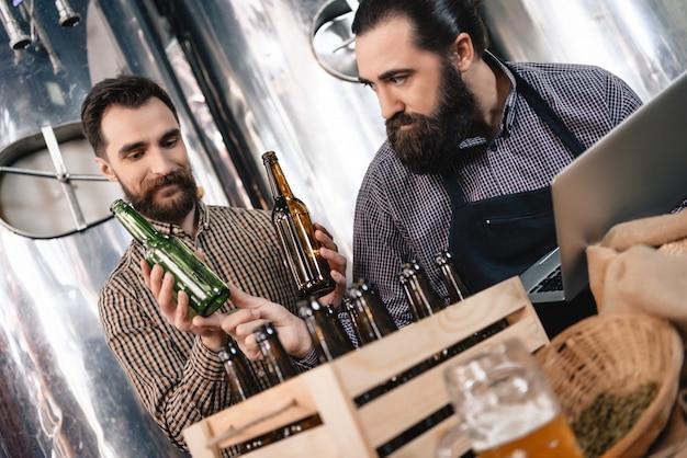 Aufmerksamer handwerker wählt bierflaschenbrauerei. Premium Fotos