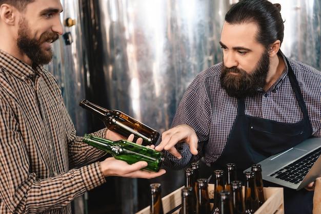 Aufmerksamer mann, der bierflaschen microbrewery wählt. Premium Fotos