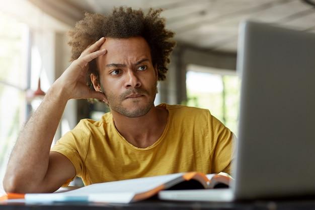 Aufmerksamer schwarzer junger mann, der drinnen vor dem geöffneten laptop sitzt und sehr ernst ist, während er online einen wissenschaftlichen artikel liest und versucht, den hauptpunkt davon zu finden und eine rezension zu diesem thema zu schreiben Kostenlose Fotos