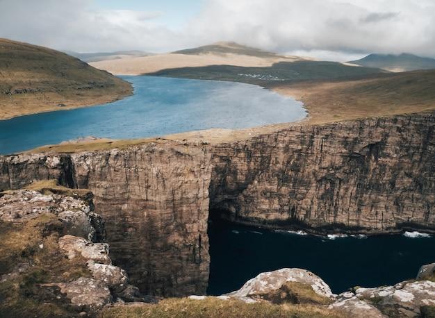 Aufnahme der wunderschönen natur der färöer, des sees, der berge und der klippen Kostenlose Fotos