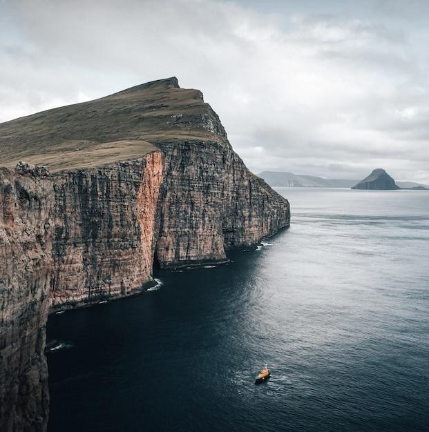 Aufnahme der wunderschönen natur der färöer, ein boot, das an den klippen im meer schwimmt Kostenlose Fotos