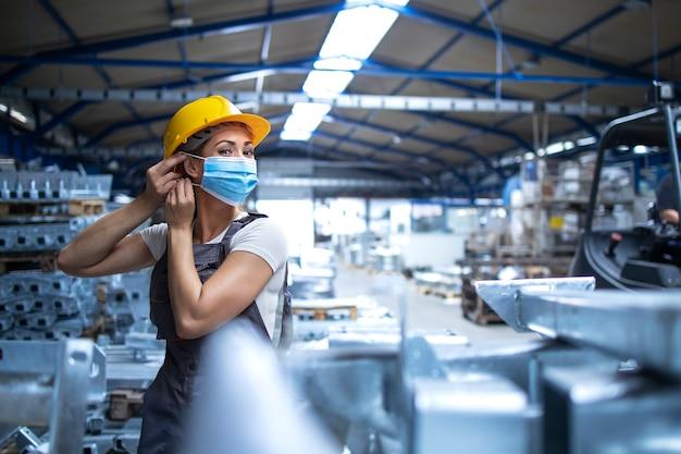 Aufnahme einer fabrikarbeiterin in uniform und helm, die eine gesichtsmaske in einer industriellen produktionsanlage aufsetzt Kostenlose Fotos