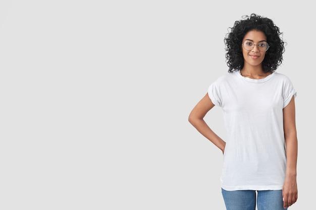 Aufnahme einer schönen journalistin, die bereit ist, ein interview zu führen, eine hand auf der taille hält, sich über einen selbstbewussten ausdruck freut, ein weißes übergroßes t-shirt, jeans und eine brille trägt und über einer leeren wand posiert Kostenlose Fotos