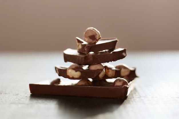 Aufnahme eines braunen tisches mit schokolade, handgefertigter pyramide aus chocholatstücken, isoliert über dunkler oberfläche, milchchocholat mit nüssen Kostenlose Fotos