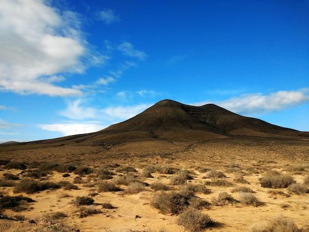 Aufnahme eines trockenen ödlands und eines berges in der ferne im naturpark corralejo, spanien Kostenlose Fotos