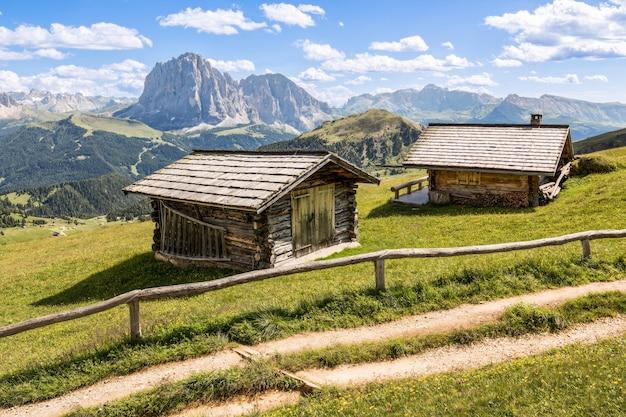 Aufnahme von zwei holzhütten auf einer wiese mit den bergen im hintergrund Kostenlose Fotos