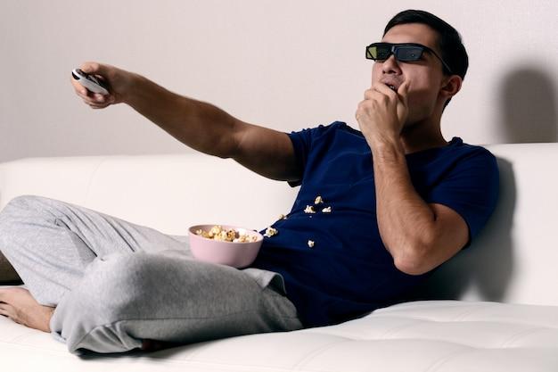 Aufpassender film des jungen mannes in den gläsern 3d und essen des popcorns Premium Fotos