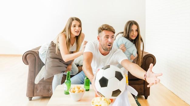 Aufpassender fußball der jungen firma am sofa Kostenlose Fotos