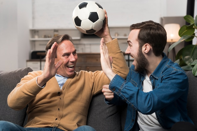 Aufpassender sport des vaters und des sohns und zujubeln im wohnzimmer Kostenlose Fotos