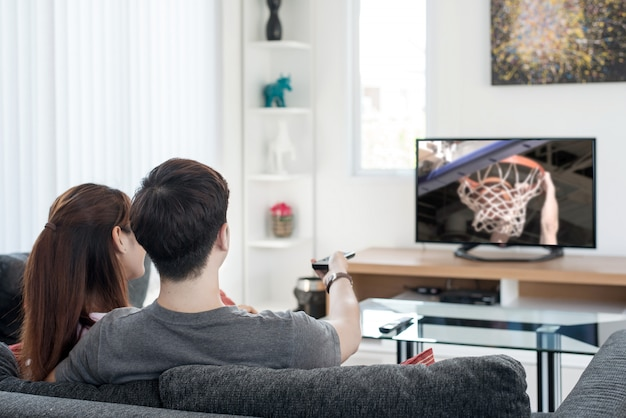 Aufpassendes basketball-sportspiel der jungen asiatischen paare im fernsehen zu hause. Premium Fotos