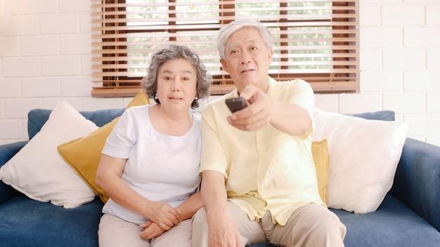 Aufpassendes fernsehen der asiatischen älteren paare im wohnzimmer zu hause, süße paare genießen liebesmoment beim auf dem sofa liegen, wenn sie zu hause entspannt werden. Kostenlose Fotos