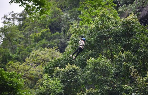 Aufregende sportabenteueraktivität der zipline, die am großen baum im wald bei vangvieng laos hängt Premium Fotos
