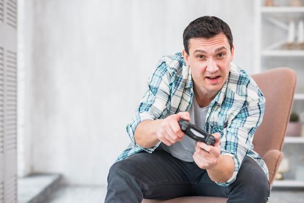 Aufregender mann, der im lehnsessel sitzt und mit gamepad spielt Kostenlose Fotos