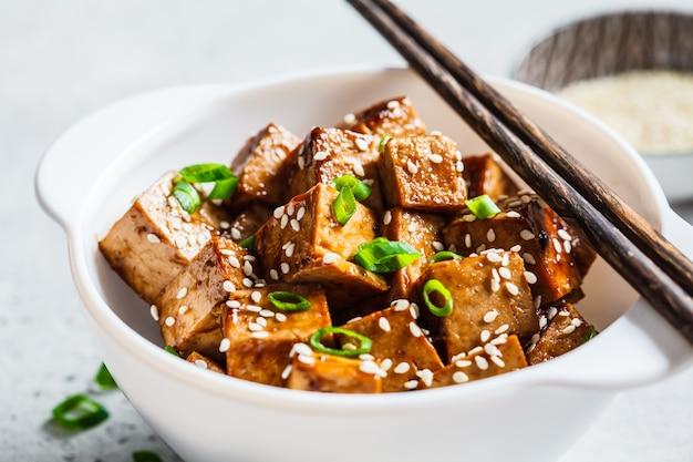 Aufruhr gebratener tofu mit samen des indischen sesams und frühlingszwiebel in der weißen schüssel. veganes food-konzept. Premium Fotos