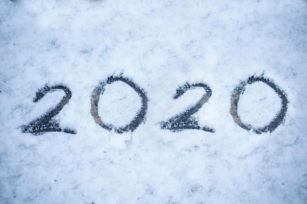Aufschrift auf dem schnee 2020. weihnachtsfeiertagshintergrund Premium Fotos