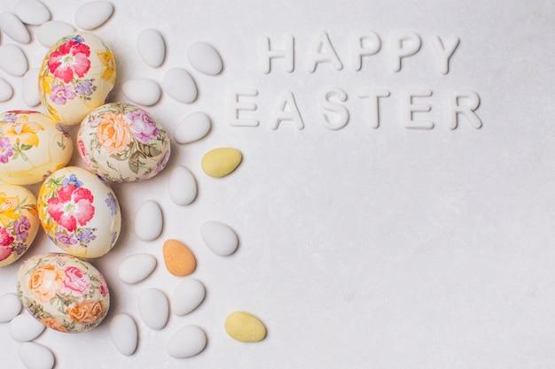 Aufschrift fröhliche ostern mit decoupaged eiern und dragees Kostenlose Fotos