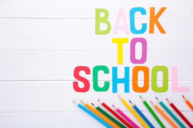 Aufschrift zurück zu schule mit schulbedarf auf weißem hölzernem hintergrund Premium Fotos