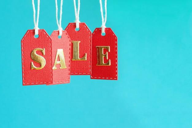 Aufschriftverkauf in den goldbuchstaben auf roten hängenden aufklebern auf einem blauen hintergrund Premium Fotos