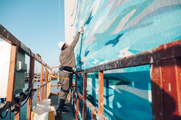 Auftragnehmer, künstler in großer höhe in einer gebäudewiege führt fassadenmalerei, dekoration und renovierung durch Premium Fotos