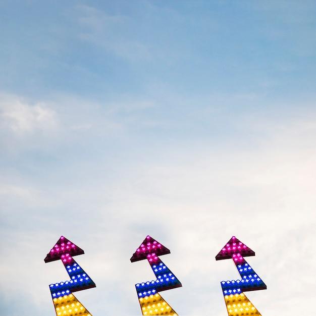 Aufwärts gerichtete ikone des blitzpfeiles gegen himmel Kostenlose Fotos