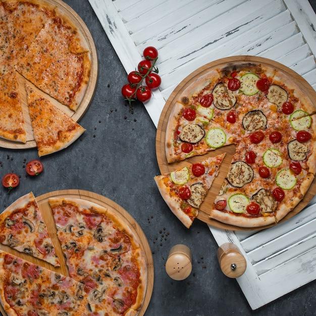 Aus drei pizzasorten geschnittene scheiben Kostenlose Fotos