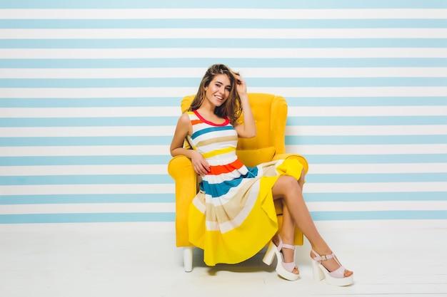 Ausdrücken von hellen positiven emotionen der freudigen modischen jungen frau im bunten kleid, das spaß im gelben stuhl auf gestreifter blauer weißer wand hat. sommerzeit, freude, lächeln, glück. Kostenlose Fotos