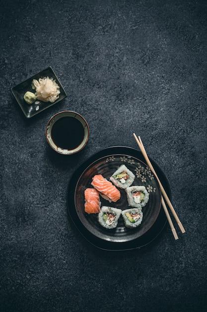 Ausgefallene sushirollen mit wasabi, ingwer und sojasauce auf schwarzer oberfläche. Premium Fotos